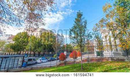 Cars parked on the side of Alfonso XII Street in Madrid, Spain, as seen from inside the fence in Retiro Park.   Unusually warm November day in one of the main parks of the city.