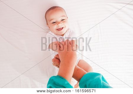 Female massaging infant hands, cute kid laughing