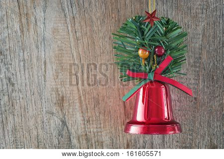 Red christmas bell with red and green bow on wooden background.