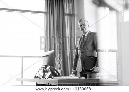 Portrait of mature businessman holding file while standing by desk in office