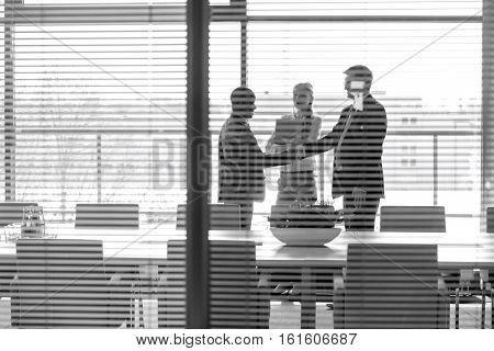 Businessmen shaking hands by female colleagues in board room seen through jalousie window