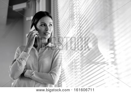 Young businesswoman using mobile phone while looking through window in office
