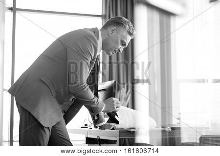 Side view of mature businessman reading book at desk in office