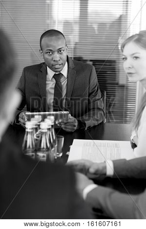 Young businessman with digital tablet having discussion with colleagues at conference table