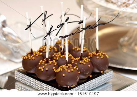 Chocolate cake pops with gold balls on top