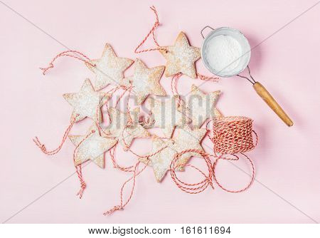 Christmas homemade gingerbread star shaped cookies with sugar powder in sieve and red decoration rope over light pink background, top view, horizontal composition