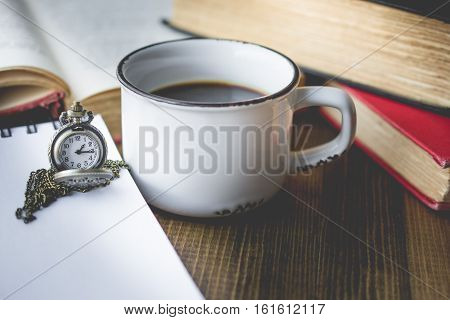 coffee in old cup and pocket watch on wooden with the book in vintage tone