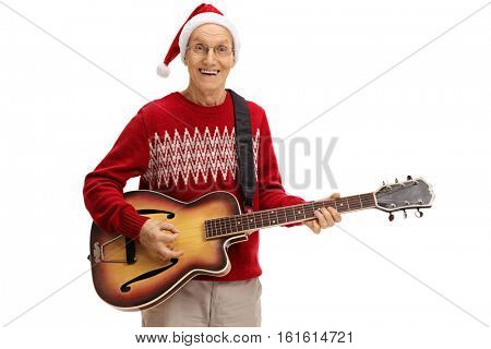 Joyful mature man with a christmas hat playing a guitar isolated on white background