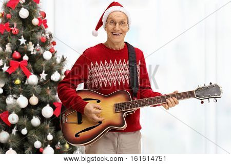 Happy senior playing an acoustic guitar in front of a christmas tree