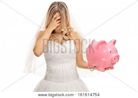 Disappointed bride holding a piggybank isolated on white background