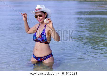 Bikini with women show beautiful hat and sunglasses on Thung Wua Lan Beach at Chumphon Province Thailand