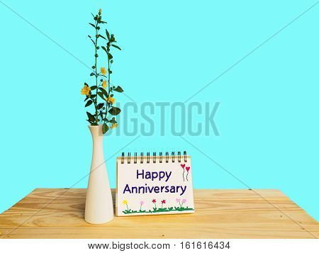 Flower branch in vase and happy anniversary message on book of wooden table and blue background with copy space
