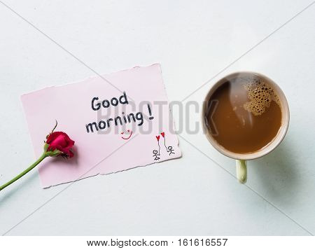 Good morning wording in note paper with red rose flowers coffee mug on white table from above breakfast valentine's day