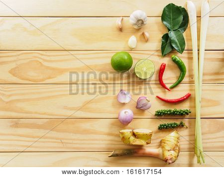 Top view organic vegetable with lemon garlic chilli peppercorn galangal begarmot and lemongrass of cooking thai food style on wooden background with copy space