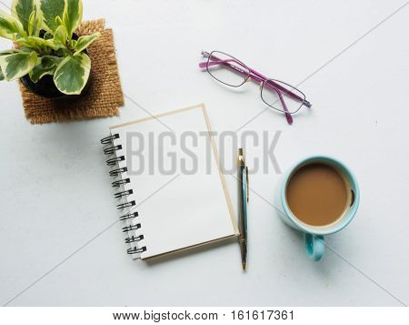 top view coffee cup, notebook, pen, glasses with plat in pot on desk of workplace