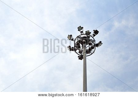 Spot-light tower at the road on blue sky background