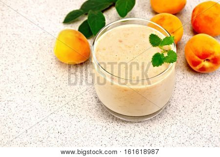 One glass of milkshake with apricots, mint on the background of a granite table