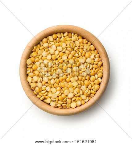 Yellow split peas in wooden bowl isolated on white background.