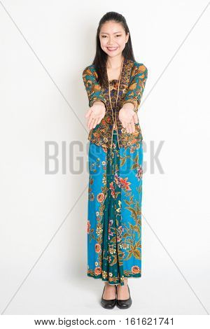 Portrait of young southeast Asian woman in traditional Malay batik kebaya dress hand holding something, full length standing on plain background.