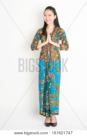 Portrait of young southeast Asian woman in traditional Malay batik kebaya dress greeting, full length standing on plain background.