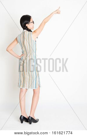 Rear view of young Asian woman in traditional qipao dress hand pointing away, full length standing on plain background.