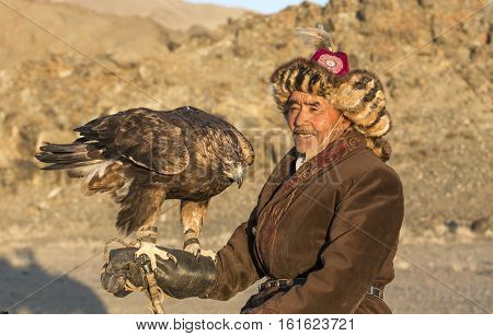 Bayan Ulgii Mongolia October 2nd 2015: Man with his  Altai Golden eagle at sunset