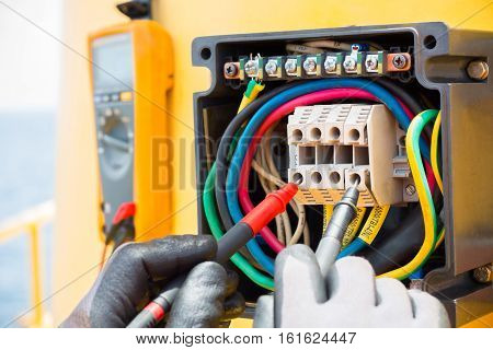 Hands of electrician with digital multimeter for checking voltage electric system junction box.