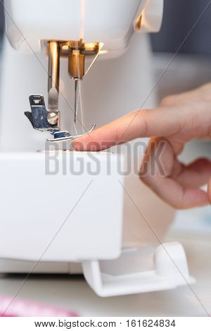 Seamstress put thread in needle