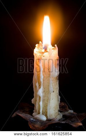 Candle ignited with wax spilling isolated in black