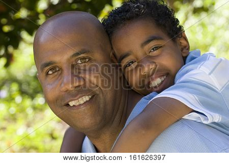 Portrait of an African American father and son outside at the park.