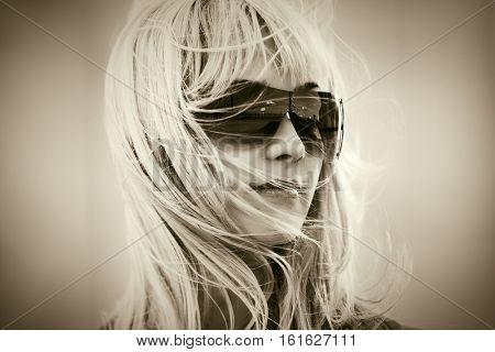 Blond woman in sunglasses walking on city street. Stylish fashion model outdoor
