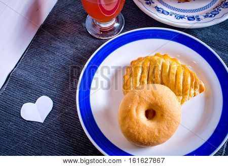 Donut And Bagel For Breakfast Or Snack With A Glass Of Orange Juice And A Small Paper Heart