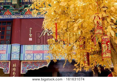 Bronkhorstspruit, South Africa - February 06, 2016: The golden Wishing Tree with red firecrackers next to the Chinese Nan Hua Temple in South Africa. Chinese New Year ceremony.