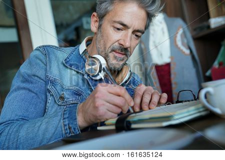 Mature man in coffee shop writing notes on agenda