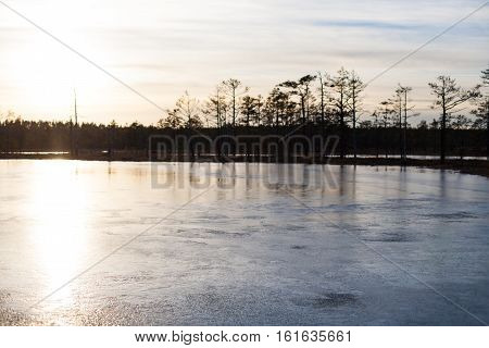 Sunset reflections on a frozen icy bog lake