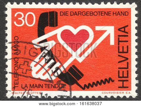 MOSCOW RUSSIA - CIRCA NOVEMBER 2016: a post stamp printed in SWITZERLAND shows the proffered hand dedicated to Pastoral Care by Phone circa 1975