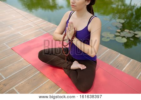 Cropped image of girl with rosary meditating