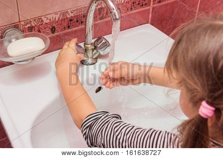 Five-year Girl Adjusts The Desired Flow And Temperature Of The Water Flowing From The Faucet Into Th