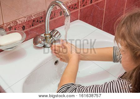 Five-year Girl Washing Her Hands In The Sink