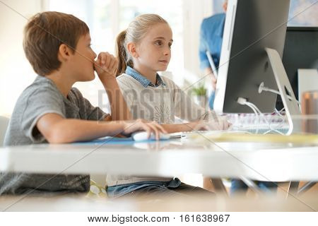 Kids in computer lab working on desktop computer