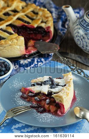 Seasonal summer berry tart with honeysuckle and rhubarb. Rustic style
