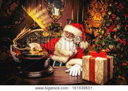 Good old Santa Claus resting at home and listens to old gramophone. Christmas songs. Christmas concept.