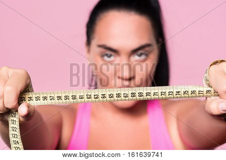 Wanting be slim. Close up of body measuring tape held by chubby mulatto woman on isolated pink background.