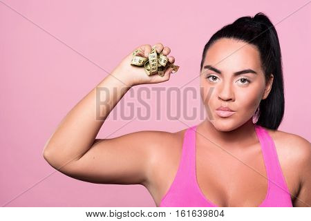 Im fed up. Close up of angry mulatto girl standing against isolated pink wall and holding crumpled body measuring tape.