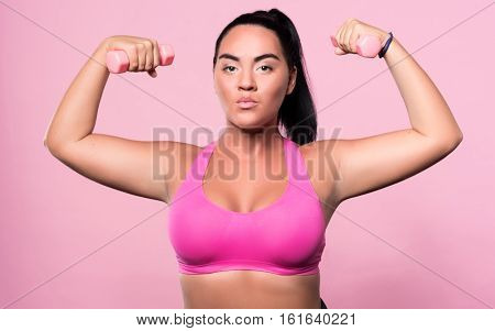 Serious attitude. Portrait of brave pretty mulatto woman standing with small dumbbells in both her hands isolated against pink background.