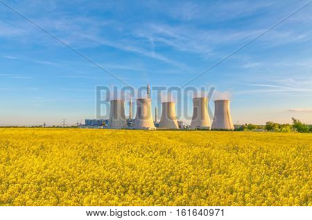 Thermal power plant with rape field, blue sky