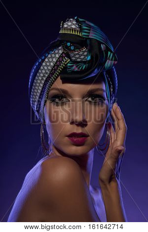 Fashionable young woman in turban looking at camera