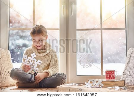 Cute little girl sitting by the window and looking at the winter forest. Child makes paper snowflakes for decoration windows. Kid enjoys the snowfall.