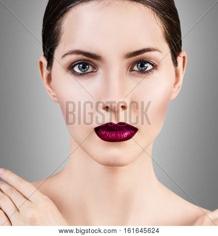 Young beautiful woman with healty fresh skin and bright make-up over gray background. Spa concept.