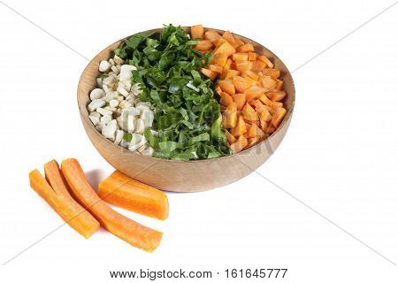 glued chopped vegetables in wooden bowl isolate on white